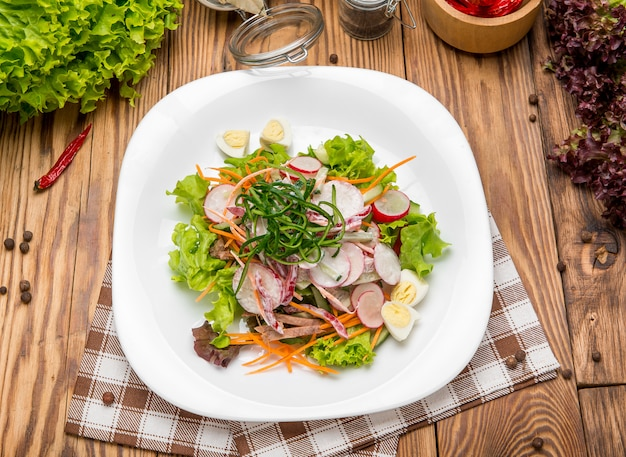 Fatias de carne picante salada de carne com cenoura, tomate, pepino, salsa, rabanete e folhas espinafre, foguete, acelga vermelha na mesa de madeira velha