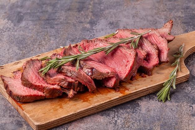 Fatias de carne rara média assada na tábua de madeira e galhos de alecrim