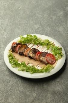 Fatias de carne servidas em fila com beringela e tomate, guarnecido com molho