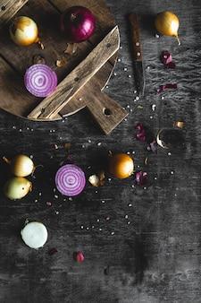Fatias de cebola roxa na placa de madeira com fundo escuro
