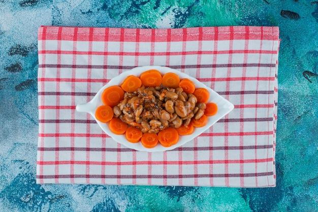 Fatias de cenoura e feijão em um prato sobre o pano de fundo azul.