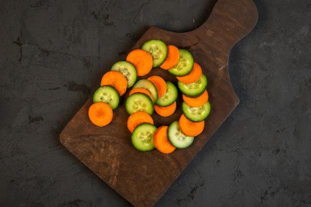 Fatias de cenoura e pepino superior na tábua de madeira em preto