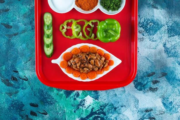 Fatias de cenoura, feijão e legumes em um prato em uma bandeja, na mesa azul.