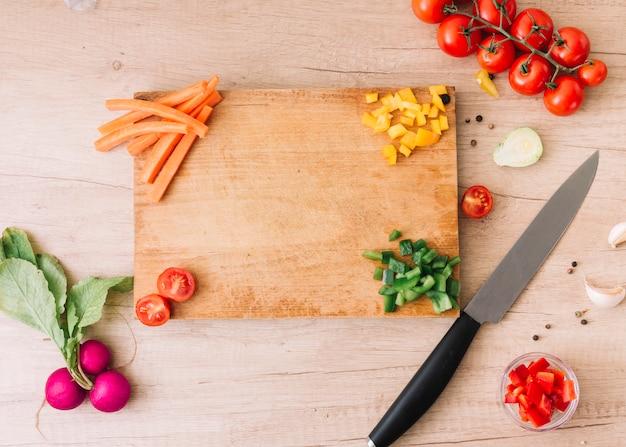 Fatias de cenoura; pimentão; tomates; beterraba; pimenta preta e dentes de alho na mesa de madeira