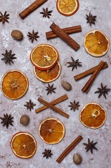 Fatias de chips de laranja secas caseiras orgânicas, nozes, anis estrelado, paus de canela na superfície marrom clara