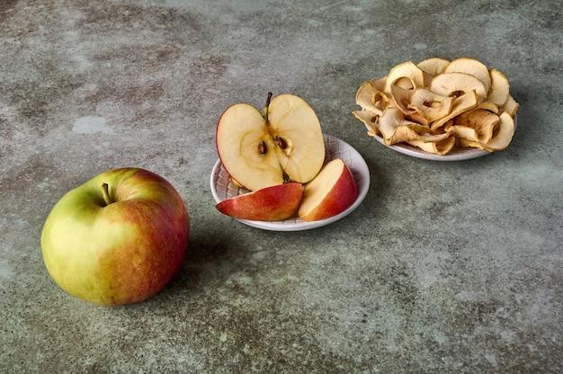 Fatias de chips de maçã e frutas de maçã no foco seletivo de vista de perspectiva de fundo de madeira rústica