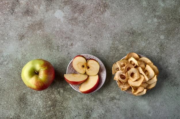 Fatias de chips de maçã e maçã em um espaço de cópia plana de fundo de madeira rústico