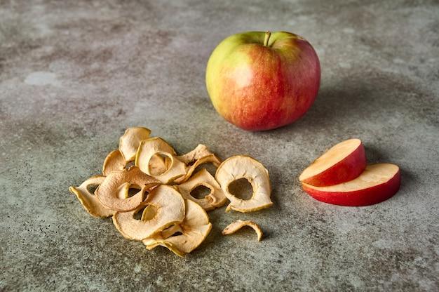 Fatias de chips de maçã e maçã em um fundo de madeira rústico fechem o foco seletivo