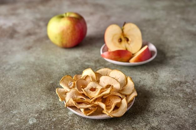 Fatias de chips de maçãs secas e maçã em um fundo de madeira rústico fechem o foco seletivo