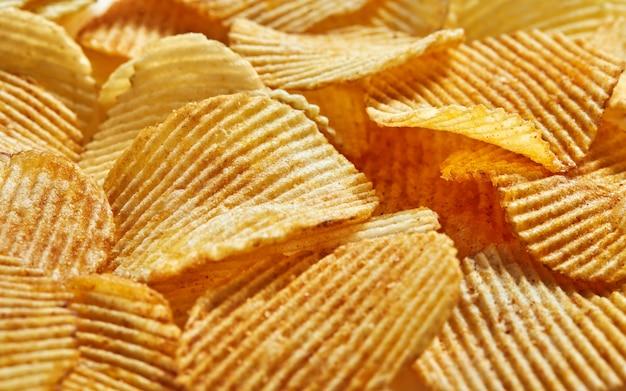 Fatias de chips dourados com listras mentindo slides textura de fundo. vista lateral