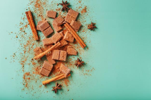 Fatias de chocolate amargo com canela e especiarias em uma superfície verde pastel