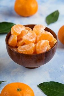 Fatias de clementina tangerina em uma tigela de madeira na superfície azul