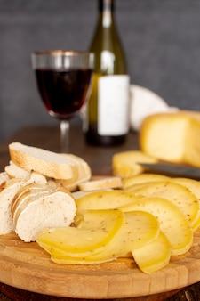 Fatias de close-up de queijo com um copo de vinho