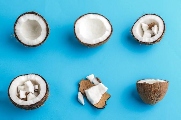 Fatias de cocos tropicais quebrados no azul. vista do topo