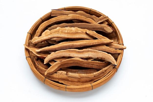 Fatias de cogumelo lingzhi secas em uma cesta de bambu em fundo branco