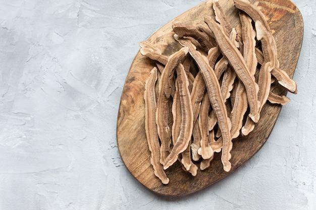 Fatias de cogumelo lingzhi seco, também chamado reishi, em uma placa de madeira