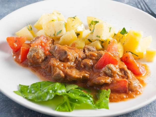 Fatias de cordeiro com batatas em molho num prato branco