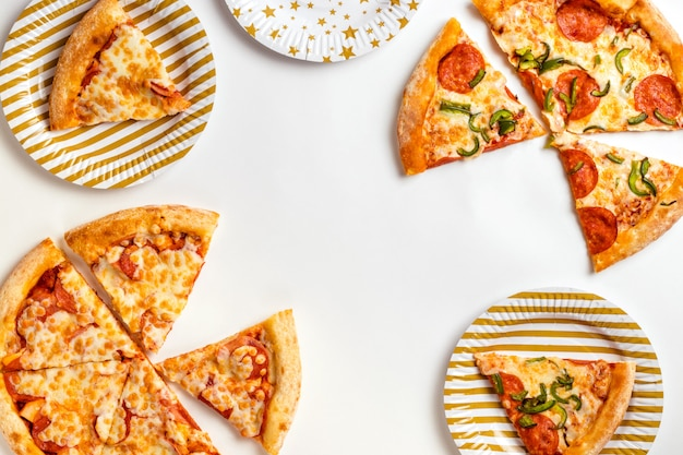 Fatias de deliciosa pizza fresca com calabresa e queijo em um fundo branco aniversário com comida lixo. vista superior com espaço de cópia de texto. configuração plana