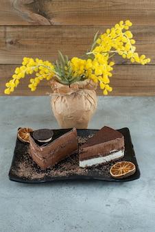 Fatias de dois bolos na placa preta com vaso de flores.