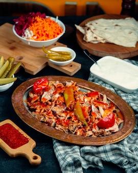 Fatias de doner de frango guarnecidas com molho de tomate, pimenta e tomate fresco