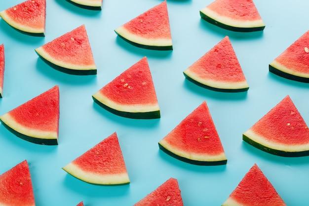 Fatias de fatias frescas de melancia vermelha e amarela no azul.