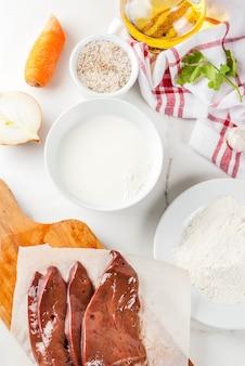 Fatias de fígado bovino cru com especiarias, ervas, leite e farinha, vista superior de mesa de mármore branco