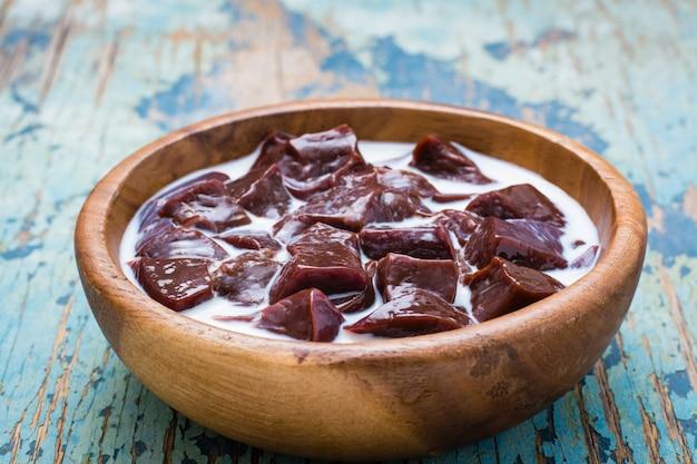 Fatias de fígado bovino cru embebido em leite em uma tigela de madeira em cima da mesa