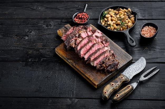 Fatias de filé de rib eye suculentas de carne média em uma tábua de servir de madeira com feijão branco e alecrim