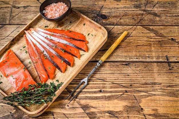 Fatias de filé de salmão salgado em bandeja de madeira com tomilho. fundo de madeira. vista do topo. copie o espaço.