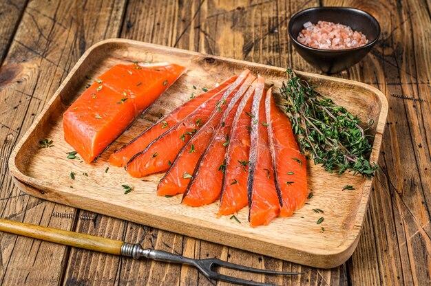 Fatias de filé de salmão salgado em uma bandeja de madeira com tomilho na mesa de madeira. vista do topo.