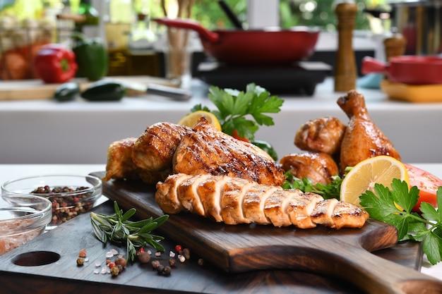 Fatias de frango grelhado com ingrediente em uma tábua de madeira na cozinha