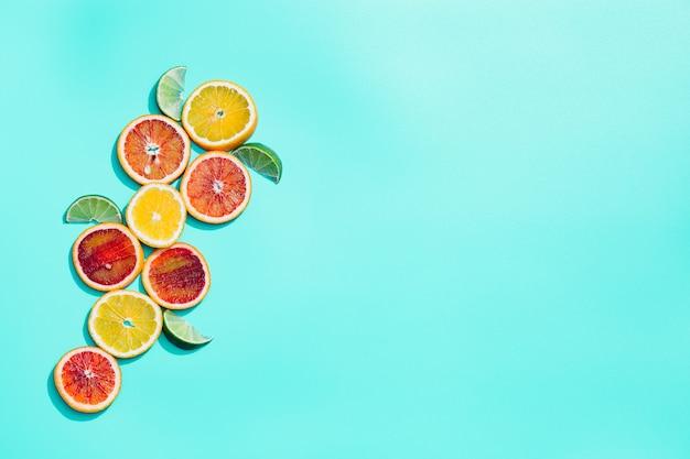 Fatias de frutas cítricas brilhantes, toranja, laranja vermelha, limão, lima em fundo turquesa pastel. fruta mínima e conceito de verão.