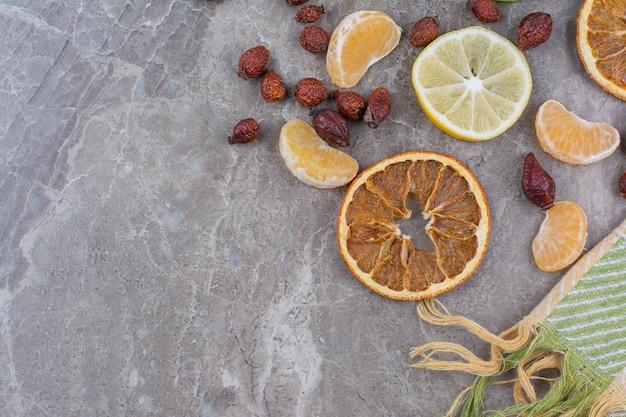 Fatias de frutas cítricas e roseiras em fundo de pedra.