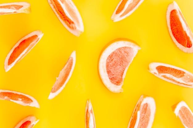 Fatias de frutas cítricas em fundo amarelo
