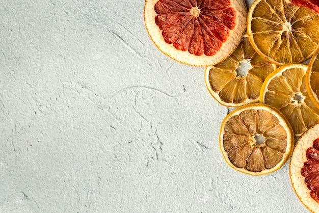 Fatias de frutas cítricas em fundo cinza textura