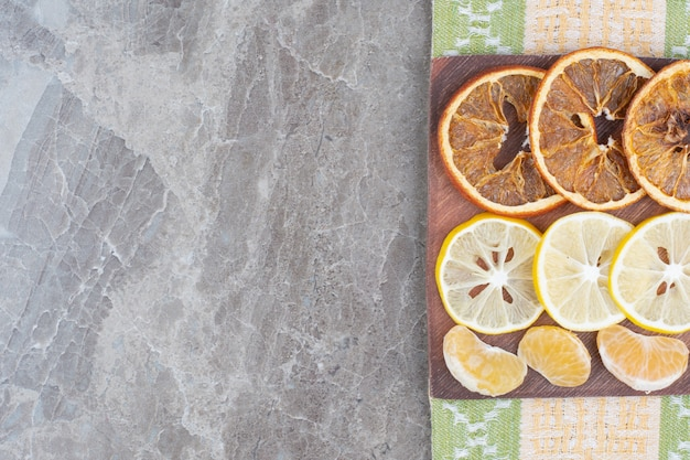 Fatias de frutas cítricas na placa de madeira com toalha de mesa.