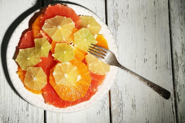 Fatias de frutas cítricas no prato, mesa de madeira