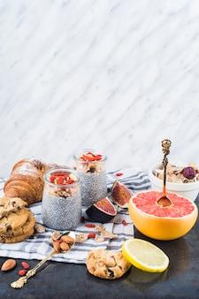 Fatias de frutas cítricas; smoothie saudável com biscoitos e croissant no guardanapo