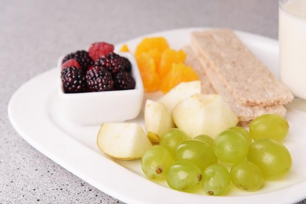 Fatias de frutas com pães crocantes e copo de leite no prato na mesa fecham