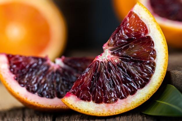 Fatias de frutas de laranjas sanguíneas da sicília sobre fundo de madeira escuro antigo.