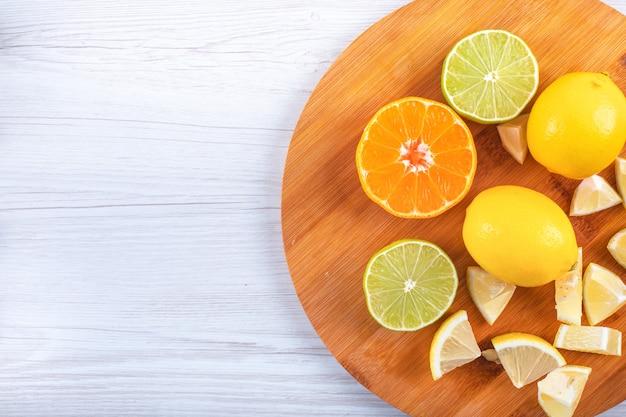 Fatias de frutas de limão verde e amarelo laranja na tábua limões frescos na mesa branca