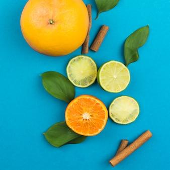 Fatias de frutas exóticas frescas perto de canela e folhagem