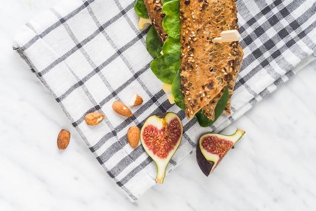 Fatias de frutas frescas de figo e amêndoas perto de cachorro-quente sobre guardanapo no balcão da cozinha
