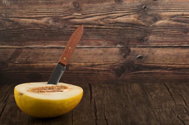Fatias de frutas frescas de melão melão doce maduro com uma faca sobre uma mesa de madeira.
