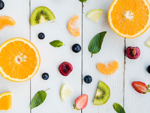 Fatias de frutas frescas tropicais brilhantes sobre fundo de madeira