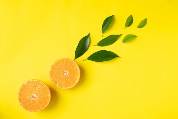 Fatias de frutas laranja com folha em fundo amarelo, copie o espaço.