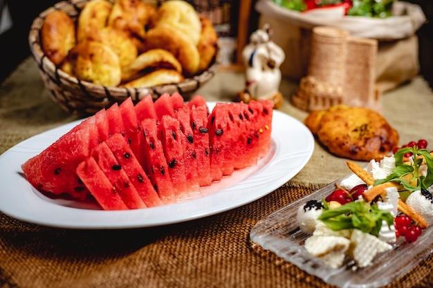 Fatias de frutas melancia servidas com queijo branco em cima da mesa
