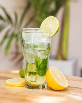 Fatias de frutas perto de copo de bebida com gelo e ervas na mesa