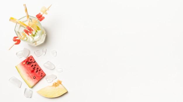 Fatias de frutas perto de gelo e título de verão em vidro com palha