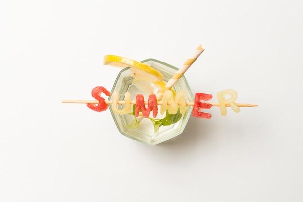 Fatias de frutas perto de gelo e título de verão em vidro